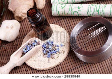 Akupunkturnadeln Handauflegen der Steinen Matte, Moxa-sticks auf Holz-Schreibtisch und Lavendel Blütenblätter mit mac
