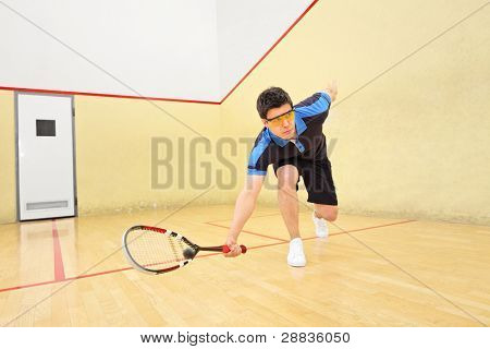 A young squash player hiting a ball in a squash court poster