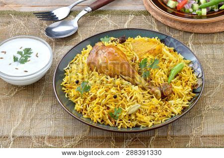 Chicken Biryani, a deleciously colorful rice dish filled with spicy marinated chicken leg piece, sal