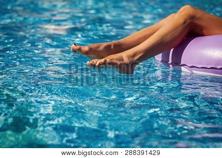 Womans Legs On The Inflatable Ring In The Swimming Pool. Summer Vacation. Enjoying Suntan. Weekend O