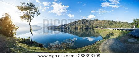 Panorama Landscape Of Wooden Bike Trail Beside Lake And Street Under Blue Sky And White Cloud At Sun