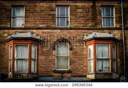 Derelict Front Of Old English House, With Smashed Windows And Dirty Curtains