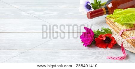 Jewish Holiday Passover Background With Flowers, Wine And Matzo On Wooden Table
