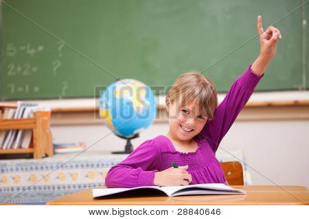 Schoolgirl raising her hand to ask a question in a classroom
