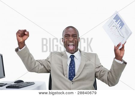 Victorious salesman with the fists up while holding a graph against a white background