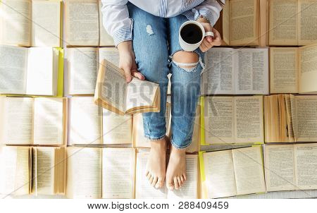 A Young Woman Reads A Book And Drinks Coffee. A Lot Of Books. Concept For World Book Day, Lifestyle,