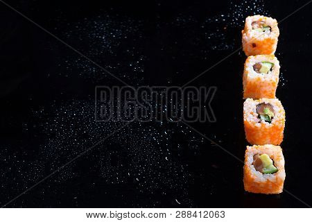 California Maki Sushi With Masago - Roll Made Of Crab Meat, Avocado, Cucumber On Glass Black Backgro