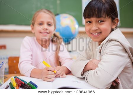 Smiling schoolgirls drawing while looking at the camera in a classroom