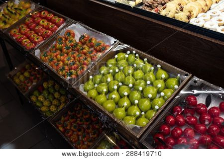 Colorful Marzipan Fruitcakes Exposed For Sale In A Store.