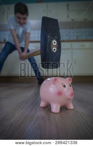 Little Boy Swinging A Big Hammer Towards A Piggy Bank. Shallow Depth Of Fiield.