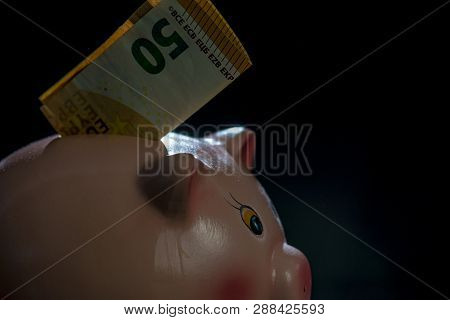 Piggy Bank On A Black Backgroud With Fifty Euro Sticking Out Of His Back