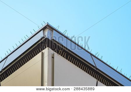 Roof Parapet. Anti-bird Spikes On Parapet Of Modern Building. Spikes For Building Elements Designed