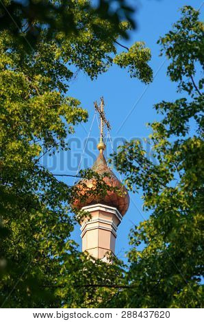 Christian Church Copper Dome With Gilded Cross Against Clear Blue Sky Behind Trees Crones