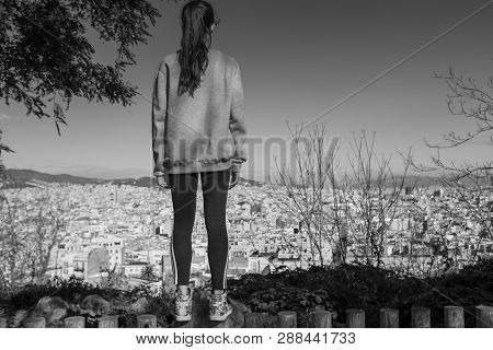 Back view of the young girl enjoying the view of the city of Barcelona from the gardens dedicated to the poet Jacinto Verdaguer, Montjuic, Spain. poster