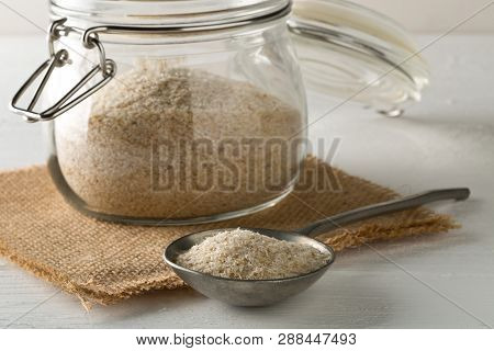 Heap Of Psyllium Husk Also Called Isabgol In Metal Spoon And Glass Jar On White Table Background. Ps