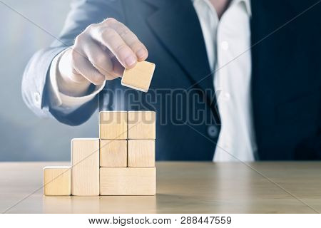Business Man Puts Next Stone On Career Ladder Made From Wooden Blocks; Career Or Achievement Concept