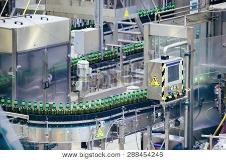 Automated Beer Bottling Production Line. Packed Beer Bottles On Conveyor Belt.