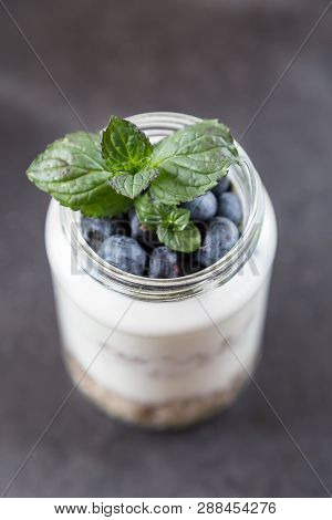 Goblet Of Yogurt With Cereals And Fruits Strewed On Leaves Mint