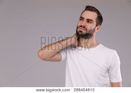 Confused Man With A Beard In A White T-shirt On A Grey Background
