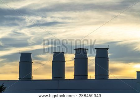 Smokestacks on top of building against scenic sky poster