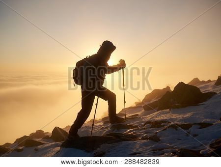 Silhouette Of Tourist Hiker With Backpack And Hiking Sticks Climbing On Rocky Mountain Peak On Copy