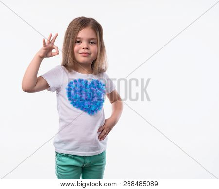 Close Up Shot Of Little Positive Girl With Long Fair Hair Looking At Camera Artistically And Shows O