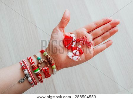Bulgarian Traditional Spring Decor Martenitsa Bracelets, Holding In Hand, Wooden Background. Baba Ma
