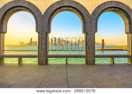 Modern Skyscrapers Of Doha West Bay Skyline At Sunset Light Through Arches Of Museum Located Along C