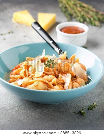 Pasta Conchiglioni (conchiglie, Shells) With Tomato Sauce, Parmesan Cheese And Thyme In A Blue Plate