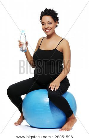 Full lenght portrait of a young smiling pregnant woman sitting on a blue ball, holding a bottle of water, isolated on a white background.