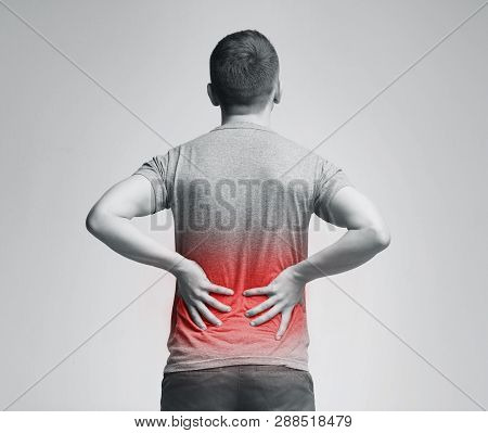 Man Holding His Hands Behind His Back, Pain In Spine, Inflamed Zone Highlighted In Red
