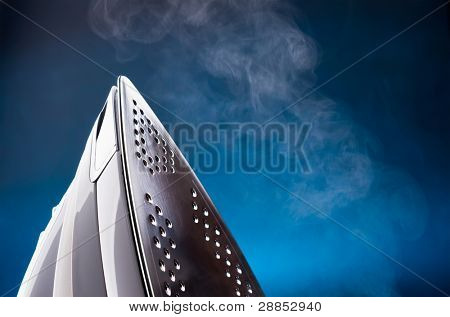 close up of ironing tool emitting steam on blue
