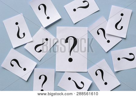 Background Of Scattered Printed Black Question Marks On White Cards With A Batch Of Smaller Cards Ar