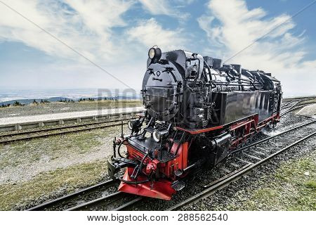 Locomotive On Railroad Tracks At A Station Under A Blue Sky