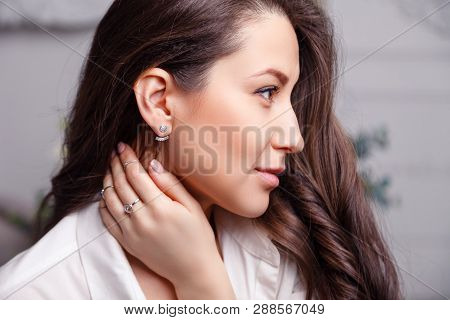 Closeup Beautiful Brunette Girl With Long Hair In Silver Jewelry Earrings, Rings, Bracelet, Chain, N