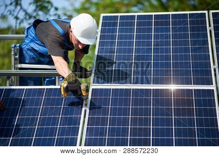 Professional Technician Standing On Ladder Connecting Solar Panel To Metal Platform Using Screwdrive