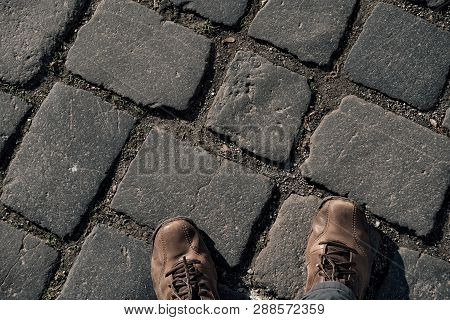 View From Above On Brown Boots On Cobblestone Pavement Background.