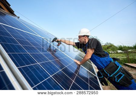 Profile Of Technician Installing Solar Panel Using Electrical Screwdriver On Blue Sky Copy Space Bac