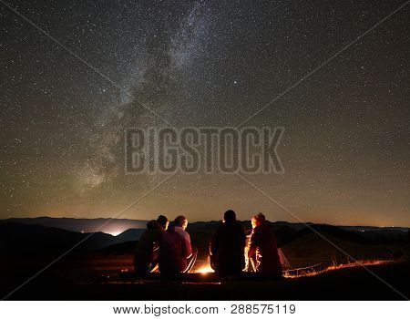 Night Summer Camping In The Mountains. Back View Group Of Four Friends Tourists Sitting On A Bench M