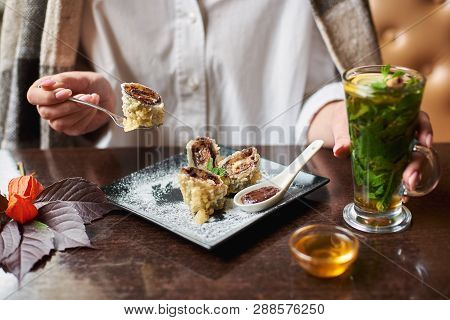 Crop Of Girl In White Holding Drink In Hand And Eating Tasty Sweet Sushi Roll With Chocolate Sauce.