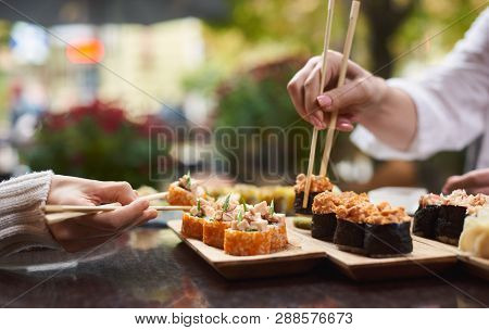 Two Women Sitting In Asian Restaurant And Eating Sushi Set With Help Of Chopsticks. Colleagues Shari