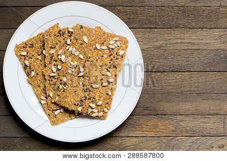 Vegan Dehydrated Raw Bread Loaves On White Plate On Wooden Table