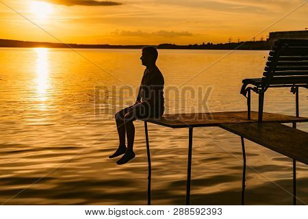Dreamy Man Sitting At The Edge Of A Masonry Over The Water At A Wonderful Sunset. Fantastic View Of