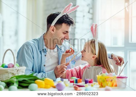 Happy Easter!dad And His Little Daughter Together Have Fun While Preparing For Easter Holidays.on Th