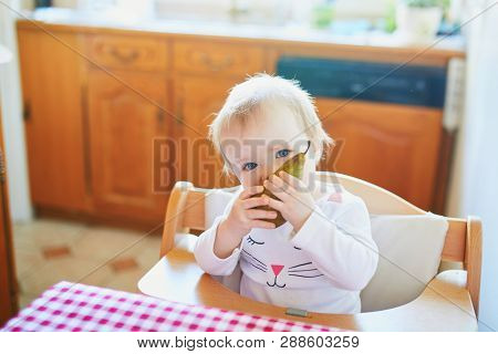Cute Baby Girl Eating Pear In The Kitchen. Little Kid Tasting Solids At Home. Baby Led Weaning