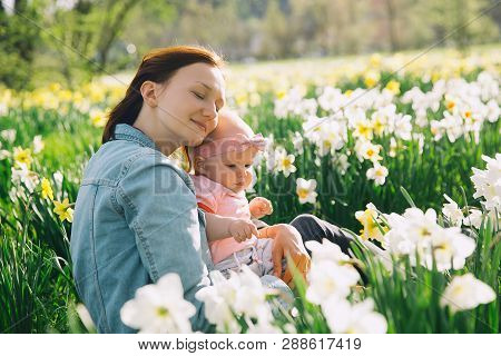 Mother And Baby Girl In Spring Park Among Blossom Field