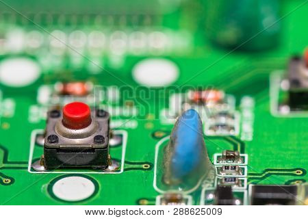 Red reset button mounted on green circuit board next to blue diode. poster