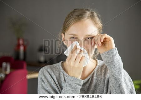 Stressed Girl Suffering From Allergy. Young Woman Covering Nose With Tissue And Moping Tears From Fa