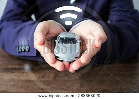 Business Man Hands Holding Car And Wifi Icon , Smart Car Concept