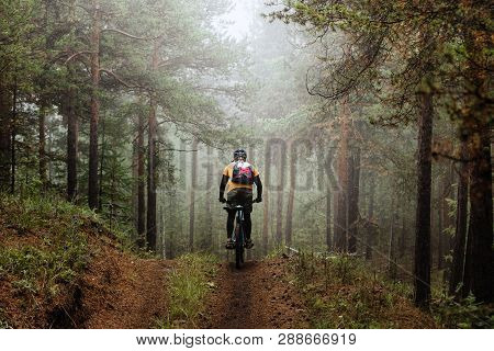 Cyclist With Backpack Riding Mountainbike On Forest Trail In Fog
